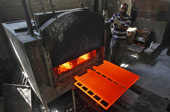A worker stands next to a room heater manufacturing unit inside a factory in Srinagar.