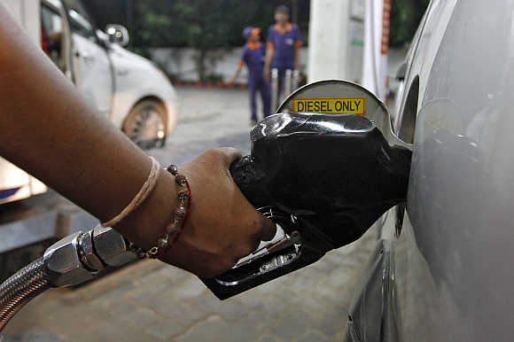 A worker fills a car with diesel at a fuel station in Ahmedabad.