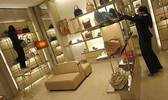 Employees adjust products inside their showroom at a mall in New Delhi.