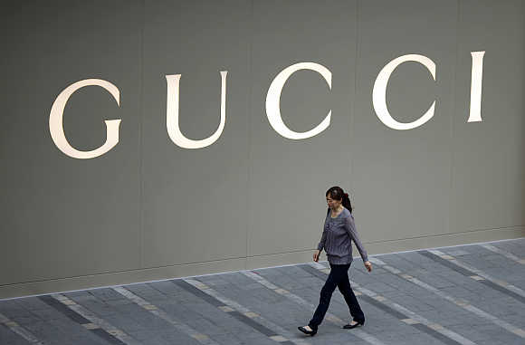 A woman walks by a Gucci luxury boutique at a mall in Shanghai.