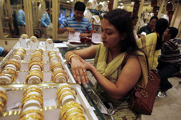 Jewellery is often pawned or sold during economic crises, she says. A woman tries on a gold bracelet in Siliguri, West Bengal.