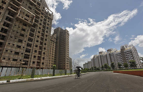 Ownership of assets itself is no panacea, says Swaminathan. A man cycles past buildings under construction in Kolkata.