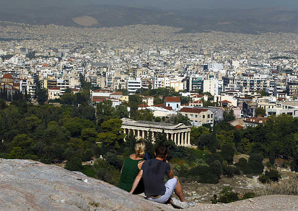 Tourists sit on a hill overlooking Athens outside the archaeological site of the Acropolis.