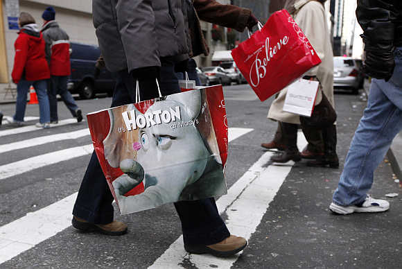 Shoppers carry bags as they walk down Fifth Avenue in New York.