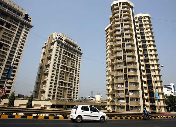 A vehicle drives past residential buildings in Mumbai.