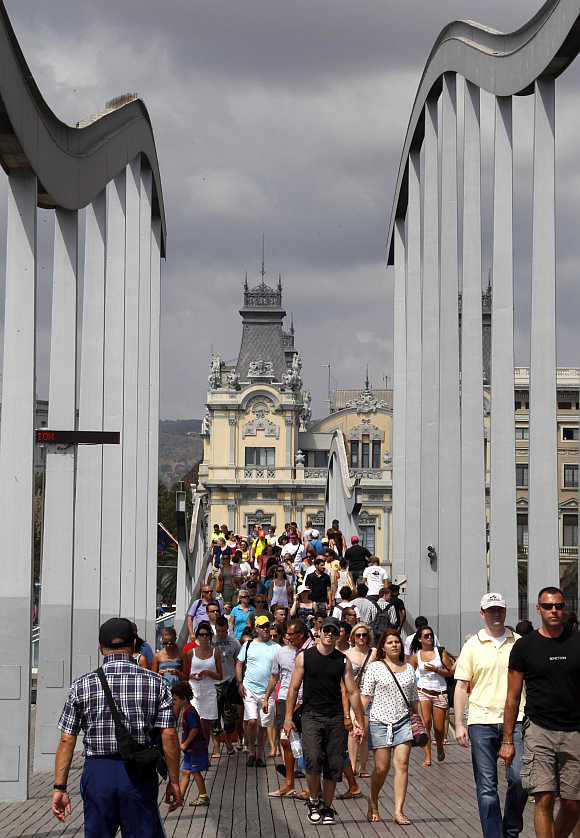 Tourists stroll along Barcelona's harbour in Barcelona.