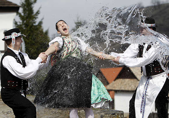 Boys hold a girl as they throw water at her as part of traditional Easter celebrations near Budapest.
