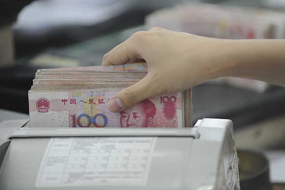 An employee counts yuan banknotes in Hefei, Anhui province, China.