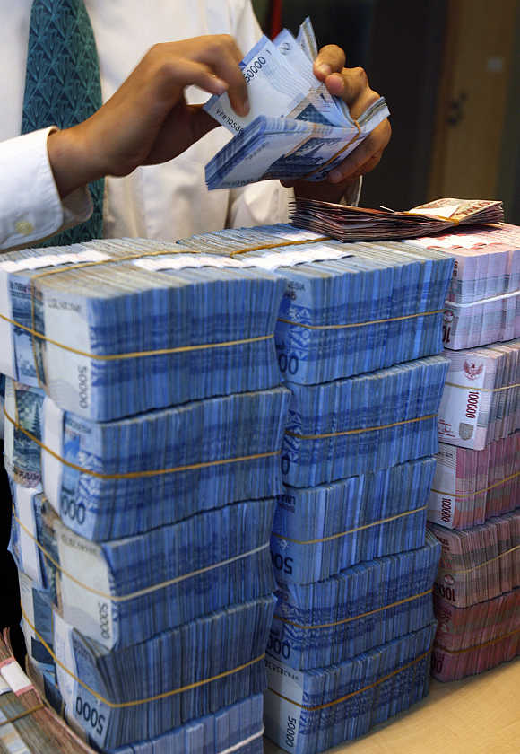 A teller counts packs of rupiah banknotes in Jakarta, Indonesia.