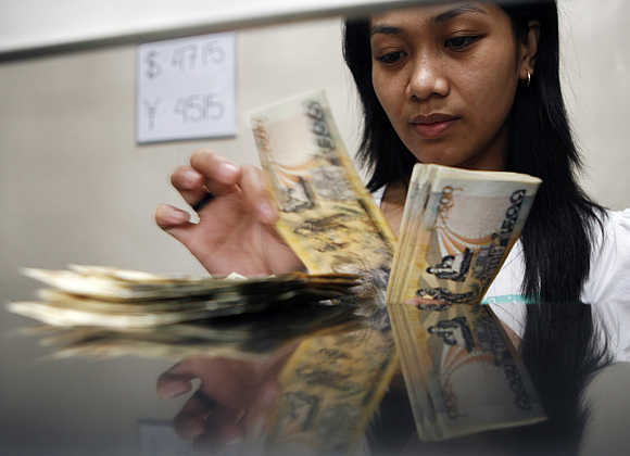 A woman counts peso notes in Manila's Makati financial district.