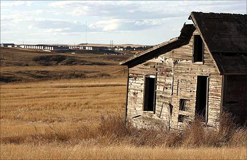 An old farm house sits near a so-called man camp outside Watford, North Dakota.