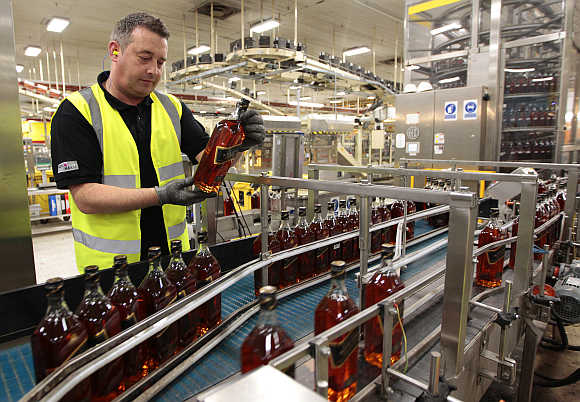 A worker looks at a bottle of Johnnie Walker whisky at the Diageo owned Shieldhall bottling plant in Glasgow, Scotland.