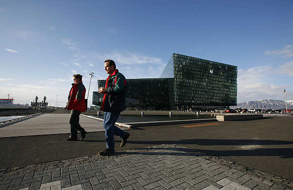 People walk past the Harpa Concert Hall in downtown Reykjavik, Iceland.