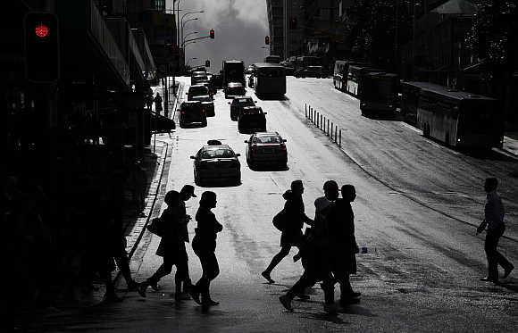 People cross a street after rainfall in central Auckland, New Zealand.
