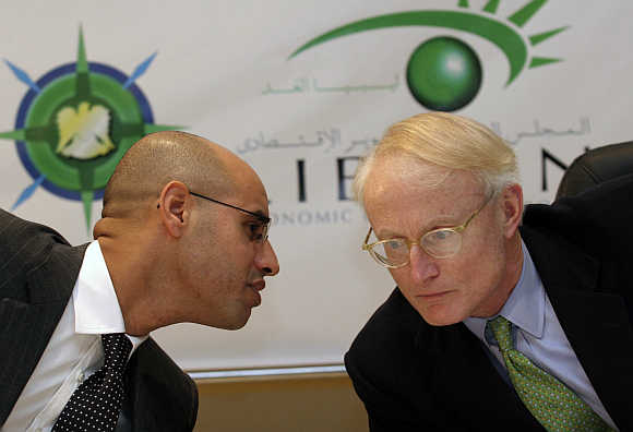 Michael E Porter, right, with Muhammad Gaddafi's son Saif Al Islam, left, in Tripoli, Libya, in a file photo.