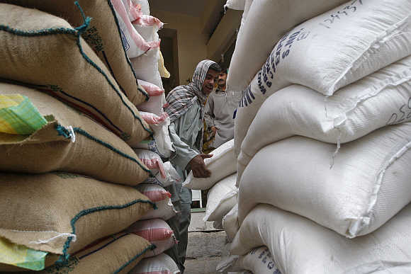 A labourer unloads sacks of rice at a shop in Karachi.