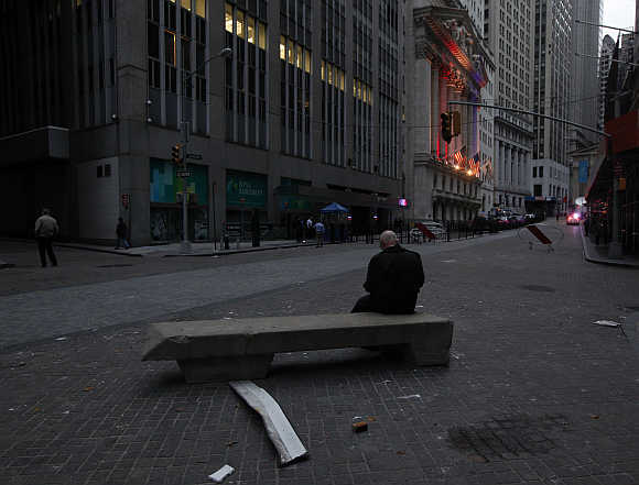 A man sits on a bench in the early morning hours outside the New York Stock Exchange.