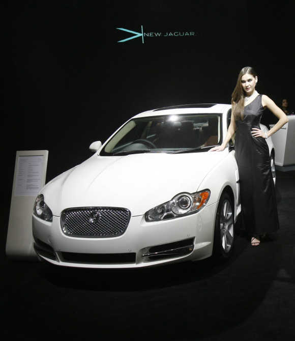 Investment has become tepid due to investor uncertainty, says Lahiri. A model poses with a Jaguar XF in New Delhi.