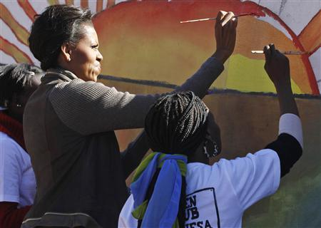U.S. first lady Michelle Obama paints a mural with teenagers in Botswana