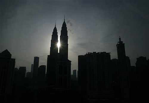 The sun rises behind the Petronas Twin Towers in Kuala Lumpur