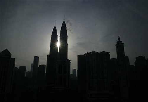 The sun rises behind the Petronas Twin Towers in Kuala Lumpur