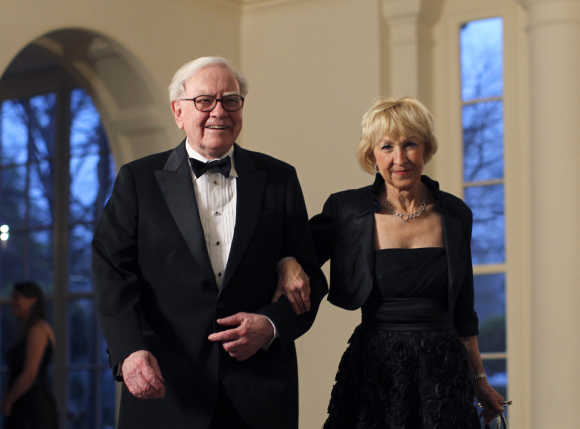 Warren Buffett and his wife Astrid Menks arrive for a State Dinner at the White House in Washington.