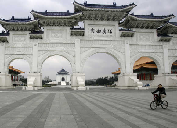 A person rides a bicycle in front of Taiwan's landmark Chiang Kai-shek Memorial hall in Taipei.