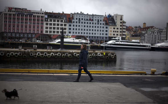 A woman walks her dog near the the marina in downtown Bergen, Norway.