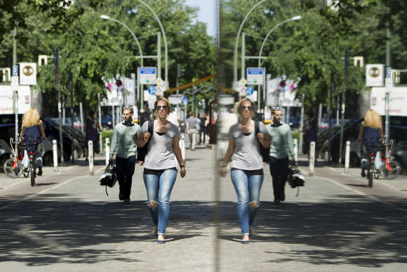 People are reflected in a shop window as they walk in Potsdamer Street in Berlin.