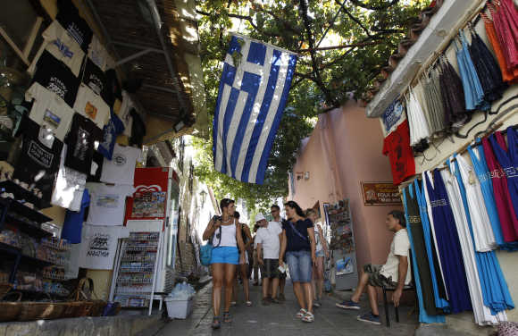 A Greek flag is seen as people walk in an alley at the tourist district of Placka in Athens.