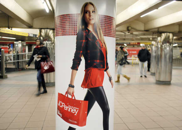 People walk past a JC Penney advertisement in a subway station in Manhattan New York.