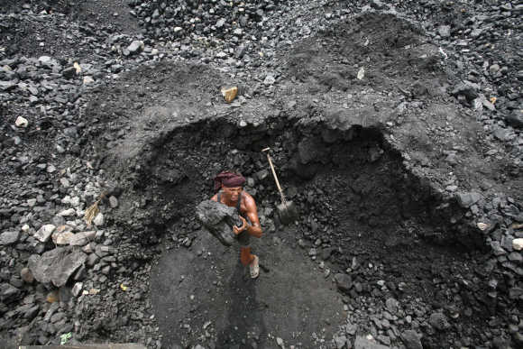 A labourer loads coal onto a truck at a yard on the outskirts of Jammu.
