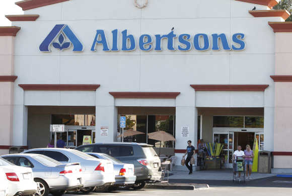 Customers leave an Albertsons grocery store with their purchases in Burbank, California. Albertsons is owned by Supervalu, the third-largest US grocery chain.
