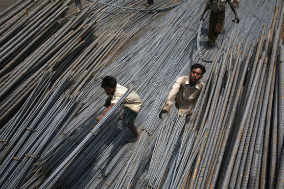 Labourers load steel rods onto a truck at a steel factory on the outskirts of Jammu.