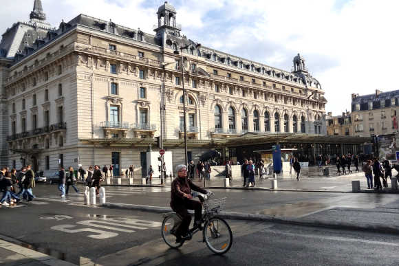 A cyclist rides past the Orsay Museum in Paris.