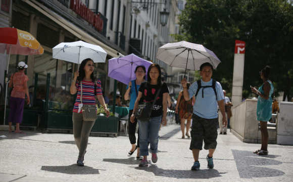 Tourists carry umbrellas as they walk in downtown Lisbon.