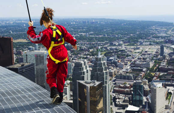 A reporter walks on the edge of the catwalk during the media preview for the 'EdgeWalk' on the CN Tower in Toronto.