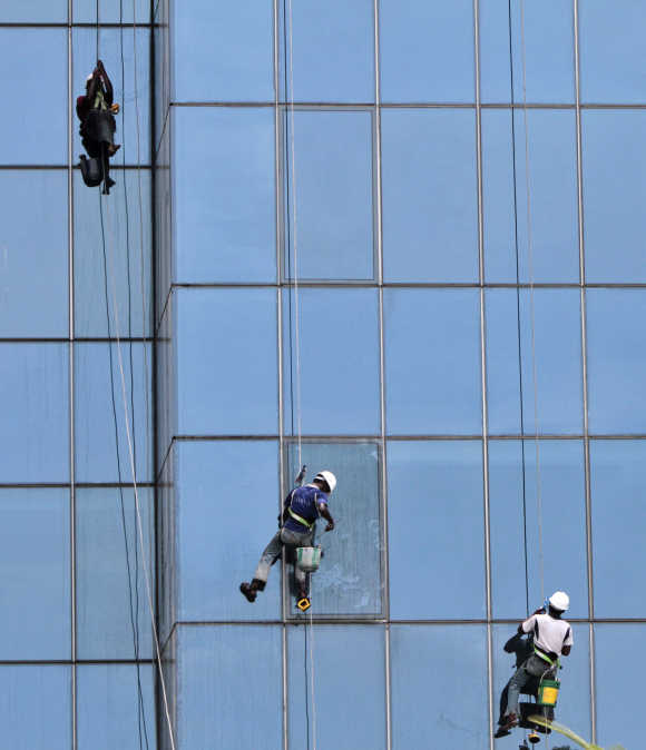 Workers suspended on ropes clean the glass facade of a commercial