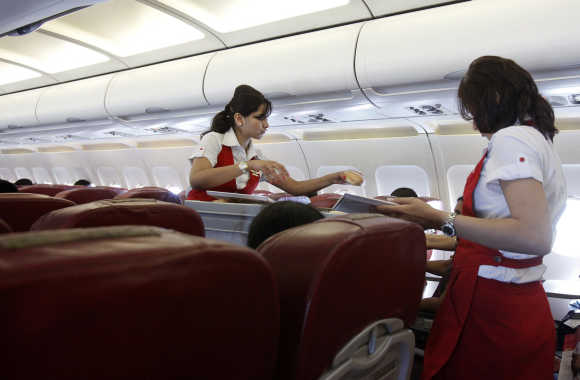 Kingfisher Airlines cabin attendants serve snacks on a flight after takeoff from Mumbai's domestic airport.