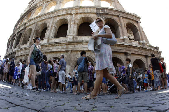 Tourists walk in front of Rome's ancient Colosseum.