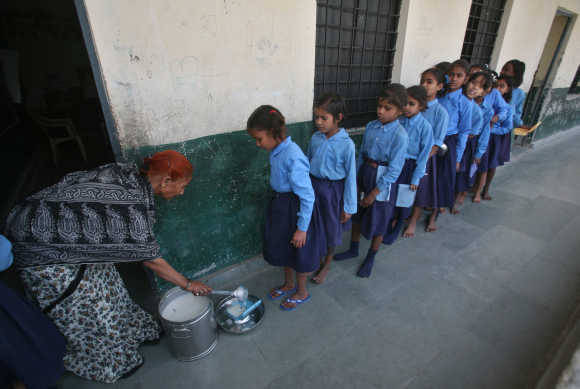 Children stand in line to collect their free mid-day meal distributed by the government inside a primary school in Noida.