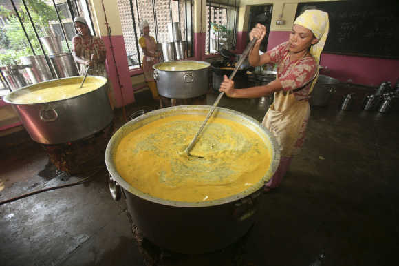 Workers prepare mid-day meal for schoolchildren at a school in Chandigarh.