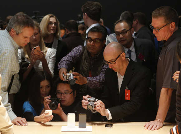 Members of the media photograph the iPhone 5 in San Francisco.