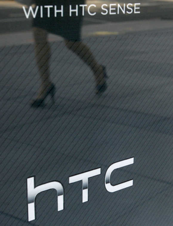 A woman walks past a HTC's window advertisement outside a mobile phone store in Taipei, Taiwan.