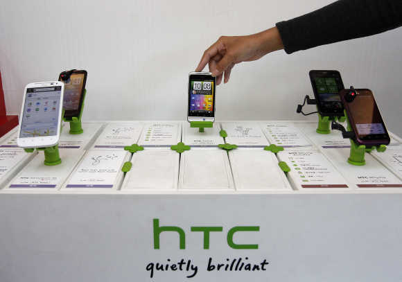 A shop attendant arranges HTC phones in a mobile phone store in Taipei, Taiwan.