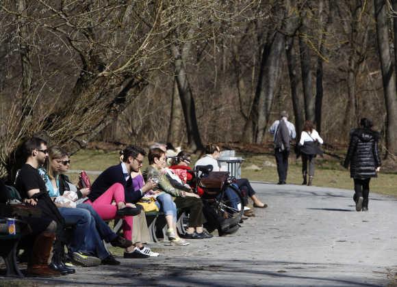 People relax in sun in Munich's English garden.