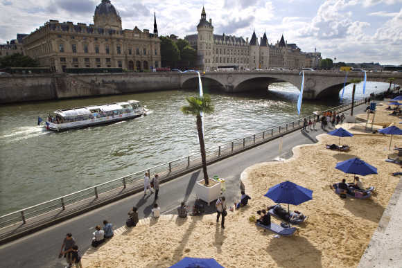 People enjoy the sun along the banks of the River Seine in Paris.