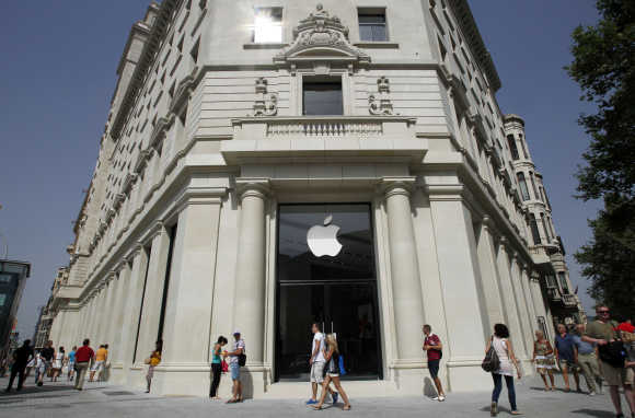People walk past the Apple store in Barcelona.