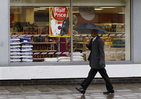 A pedestrian walks past a Tesco store in London.