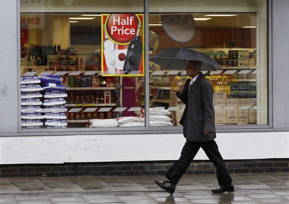 A pedestrian walks past a Tesco store in London.
